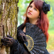 Royalty-Free Stock Photo: Gothic girl with a fan in the park