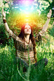 Young woman meditating in the garden — Stock Photo