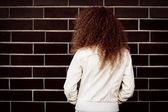 Kadın kıvırcık saçlı duran tuğla duvar arka plan — Stok fotoğraf