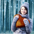 Outdoor winter portrait of young pretty girl with brown heart in her hands — Stock Photo