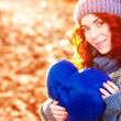 Stock Photo: Golden autumn portrait of young pretty girl with blue heart in her hands