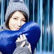 Outdoor winter portrait of young pretty girl with blue heart in her hands — Foto Stock