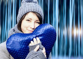 Outdoor winter portrait of young pretty girl with blue heart in her hands — Stock Photo