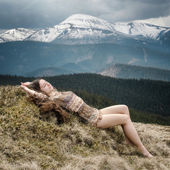 Young woman laying on a hillside in the mountains — Foto Stock