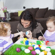 Mother painting easter eggs with children — Stock Photo #39917899