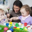 Mother painting easter eggs with children — Stock Photo