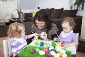 Mère peignant des oeufs de Pâques avec les enfants — Photo