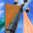 Street lamp with colorful flags - Stock Photo
