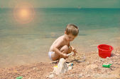 The child plays on the seashore. — Stock Photo
