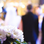 Flowers with a wedding ceremony in background — Stock Photo