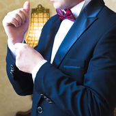 Close-up of a man in a tux fixing his cufflink — Stock Photo