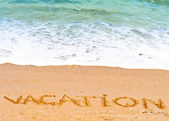 Vacation word written in the sand on the beach blue waves in the background — Stock Photo