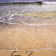 Euro sign and question mark in the sand, washed away by sea water — Stockfoto