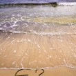 Euro sign and question mark in the sand, washed away by sea water — Foto de Stock