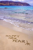 Happy new year and exclamation point written in the sand — Stock Photo