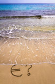 Euro sign and question mark in the sand, washed away by sea water — Stock Photo