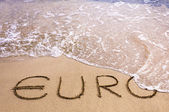 Euro word written in the sand on a beach, washed away by sea water — Stock Photo