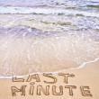 Last Minute written on sand, being washed away by waves — Stock Photo #33703901