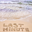 Last Minute written on sand, with waves in background — Stockfoto
