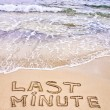 Last Minute written on sand, with waves in background — Stock fotografie