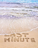 Last Minute written on sand, being washed away by waves — Stockfoto