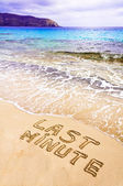 Last Minute written on sand, with waves in background — Stock Photo
