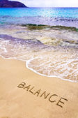 Word BALANCE written on sand, with sea waves in background — Stock Photo