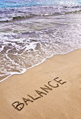 Word BALANCE written on sand, with sea waves in background — Foto Stock