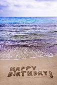 Happy Birthday written on the beach — Stok fotoğraf