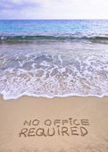 No office required written on sand, blue ocean water in background — Stock Photo