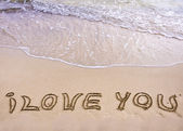 Words I LOVE YOU written on sand, with wave in background — Stock Photo