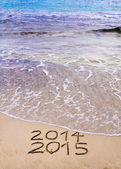 New Year 2015 is coming concept - inscription 2014 and 2015 on a beach sand, the wave is covering 2014 — Stock Photo