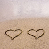 Symbols of two hearts drawn on sand, love concept — Stock Photo