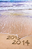 New Year 2014 is coming concept - inscription 2013 and 2014 on a beach sand, the wave is covering 2013 — Stock Photo