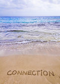 Connection word written on sand, with waves in background — Stock Photo
