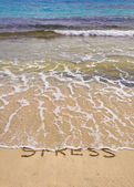 Words Stress written on sand, washed away by waves — Stock Photo
