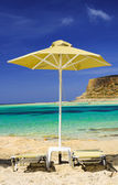 Tropical vacation - beds and umbrella on a beach — Stock Photo