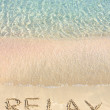 Relax word written in the sand, on a beautiful beach with clear blue waves in background — Stock Photo