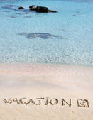 Vacation and checked mark written on sand on a beautiful beach, blue waves in background — Zdjęcie stockowe