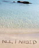 All I need message written on white sand, with tropical sea waves in background — Stock Photo