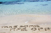 TAKE SOME TIME OFF written on sand on a beautiful beach, blue waves in background — Stock Photo