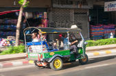 Bangkok, Thailand - May 23, 2014: Unidentified driver and tourists in tuk-tuk vehicle along the roads of Bangkok, Thailand. The tuk-tuk is a widely used form of urban transport in Bangkok. — Stock Photo