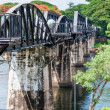 "Kanchanaburi, Thailand - May 23, 2014: Tourists visiting the bridge over River Kwai in Kanchanaburi, Thailand.The bridge is famous due to the movie ""The Bridge on the River Kwai"". — Stock Photo #48467403"