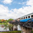 "Kanchanaburi, Thailand - May 23, 2014: Train on the bridge over river Kwai in Kanchanaburi province, Thailand.The bridge is famous due to the movie ""The Bridge on the River Kwai"". — Stock Photo #48478325"