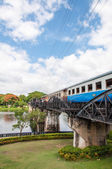 "Kanchanaburi, Thailand - May 23, 2014: Train on the bridge over river Kwai in Kanchanaburi province, Thailand.The bridge is famous due to the movie ""The Bridge on the River Kwai"". — Photo"