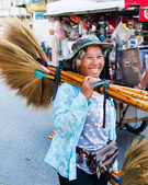 Maeklong, Thailand - May 24, 2014: Unknown Street vendor of traditional made brooms.Street vending is very common in Thailand and also a main tourist attraction. — Stock Photo