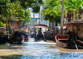 Thai locals sell food and souvenirs at famous Damnoen Saduak floating market in Thailand, in the old traditional way of selling from small boats. — Stock Photo