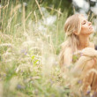 Beautiful young blonde woman in summer - Stock Photo