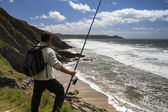 A sea angler gazes over the surf, cliffs and sea. — Stock Photo