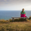 A Blonde Female Hiker Rests on a Bench on the Cliffs. — Stock Photo